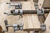 Using Clamps And Glue To Connect Wooden Timbers For Furniture Detail. poster
