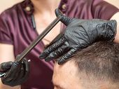 Female Making Modern Hairdo For Client, Close Up View. Stylists Hands In Black Rubber Gloves Cutting poster