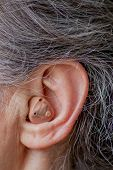 Closeup Senior Woman Inserting Hearing Aid In Her Ears poster