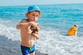 Little Baby Boy Playing On The Beach By The Sea In Sand And Stones. Build Sand Castles. Games And En poster