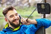 A Handsome Young Man Smiles During A Pleasant Telephone Conversation In Nature, Using An Outdated Pu poster