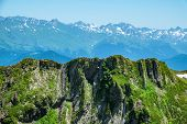 Mountain Range With Rocks And Snow On Slopes Against A Clear Blue Sky. Mountain Peak In The Summer.  poster