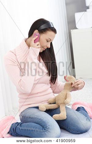 Junges Mädchen talking on Mobile Phone, Stofftier Hase in der hand halten.