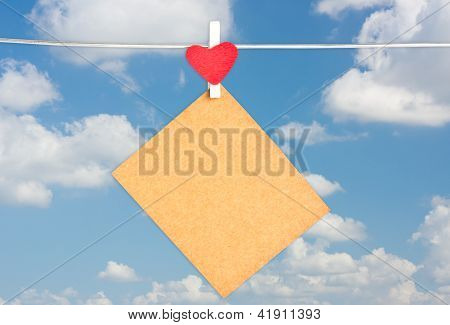 Blank Brown Paper Hanging On The Clothesline With Blue Sky Background.