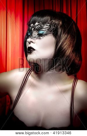 Young actress with venetian mask over cabaret background
