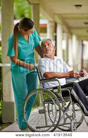 Nurse talking to elderly man in wheelchair in a nursing home