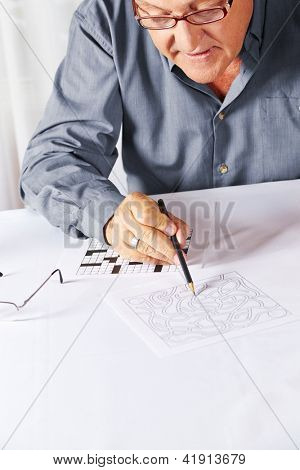 Senior with reading glasses solving a riddle in a rest home