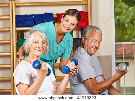 Two senior people in gym doing fitness exercises with dumbbells