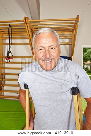 Happy senior man using crutches in a gym