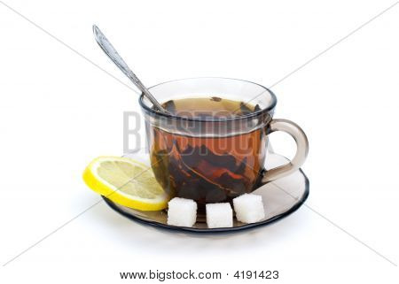 Teacup With Black Tea, Teaspoon, Dish, Lemon Slice And Some Sugar Pieces