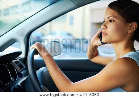 businesswoman driving car and talking on cell phone concentrating on the road