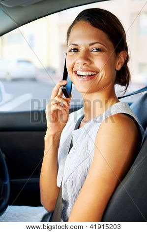 attractive businesswoman smiling while talking on the phone and driving to work, happy carefree business