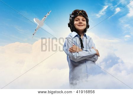 Image of little boy in pilots helmet with flying airplane in background
