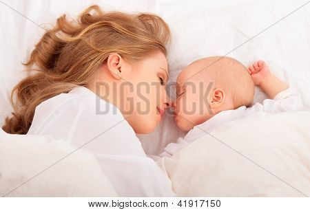 Sleeping Together. Mother Embraces The Newborn Baby In Bed