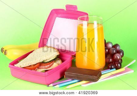 Lunch box with sandwich,fruit,juice and stationery on green background