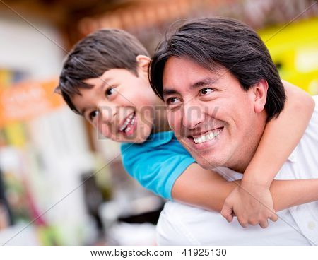 Happy father playing with his son and smiling