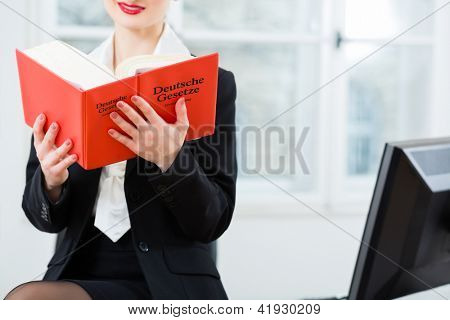 Young female lawyer working n her office reading in a typical law book