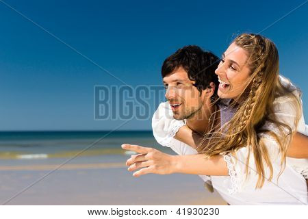 Playful couple on the ocean beach enjoying their summer vacation, the man is carrying the woman piggyback