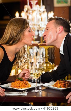 glückliches Paar haben ein romantisches Date in ein Gourmetrestaurant fressen sie Spaghetti, eine große Kronleuchter