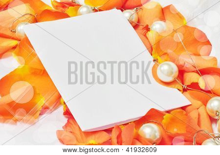 Sheet Of White Paper On Orange Petals Of Roses And Pearls