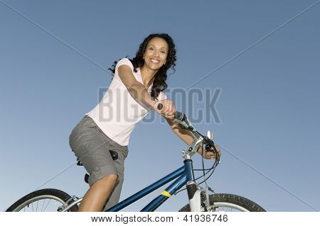 Low angle view of an African American woman cycling against blue sky
