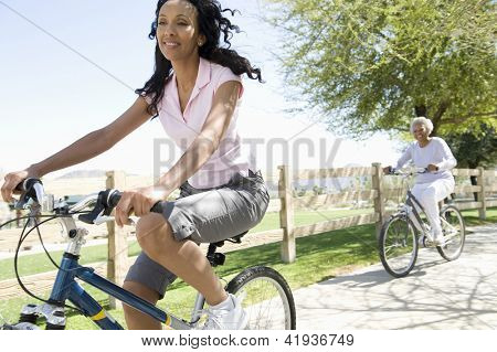 A happy African American woman cycling with her mother in park