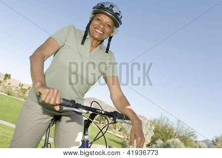Portrait of a happy African American senior woman sitting on bicycle in park