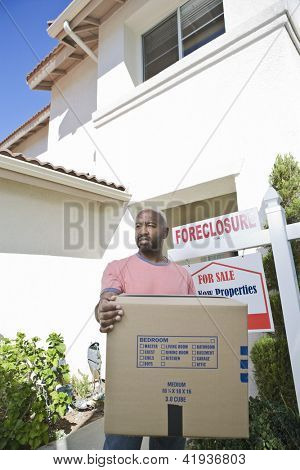 Sad man carrying cardboard box while moving out of the house