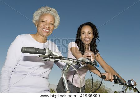 Portrait of happy African American mother and daughter sitting on bicycle against blue sky