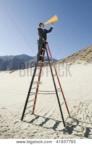 Full length of a businessman standing on ladder and yelling through megaphone in desert