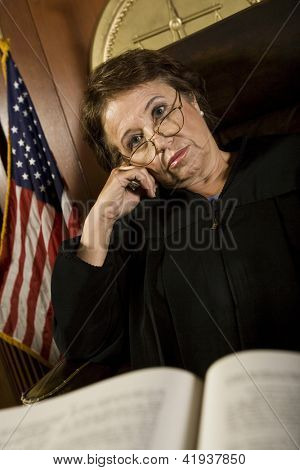 Tired senior judge sitting with book in courtroom
