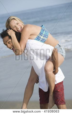 Portrait of jovial multi ethnic couple having fun on beach