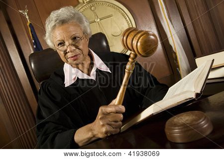Senior judge sitting with book and mallet in courtroom