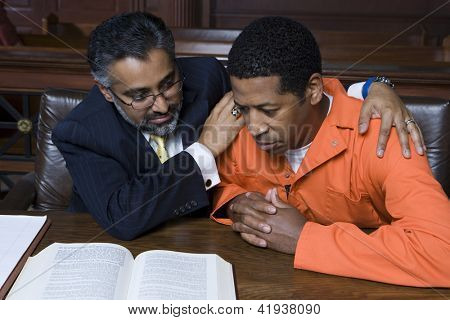 African American criminal sitting with advocate in courtroom