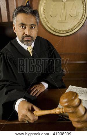 Retrato de juez sostiene el mazo en sala