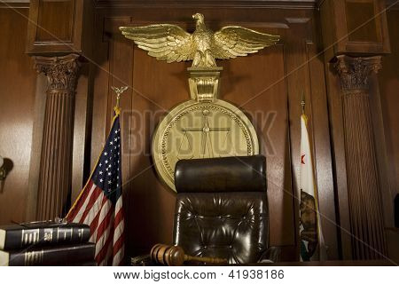 Judge chair with mallet on table in courtroom