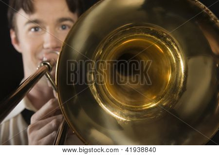 Portrait of a man playing trombone isolated over black background