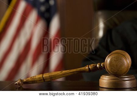 Close up of gavel with American flag in the background in courtroom