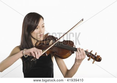 Young woman playing violin isolated over white background