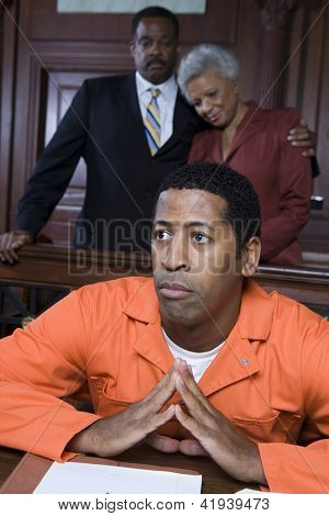 Sad criminal sitting in court with parents standing behind him