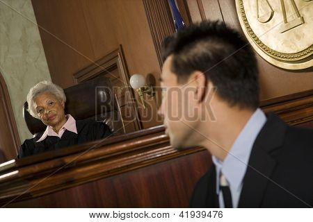 Judge and lawyer looking at each other in courtroom