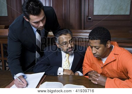 African American criminal sitting with two advocates in courtroom