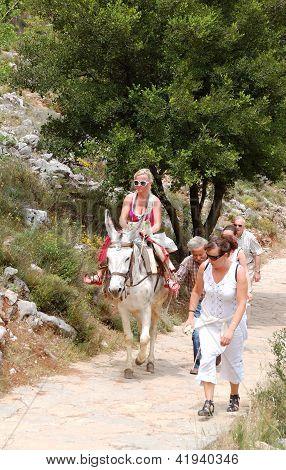 Crete Island, Greece - May 13: The Female Tourist On A Donkey And Local Greek Man Controls The Anima
