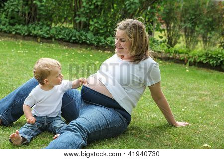 Pregnant Woman And Little Son In Summer Garden