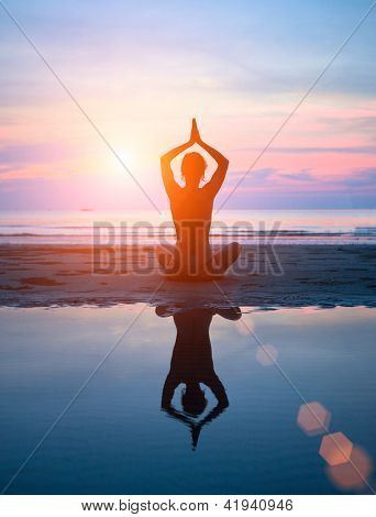 Silhouette of a woman yoga on sea sunset with reflection in water.