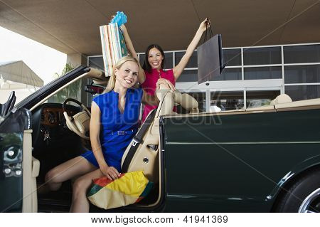 Excited female friends with shopping bags in convertible car