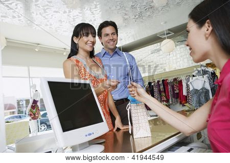 Happy couple paying with credit card in store
