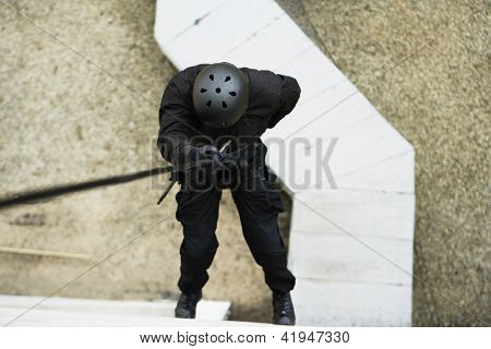 High angle view of man rappelling down outside building