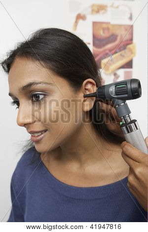 Female doctor doing ear examination with otoscope on patient