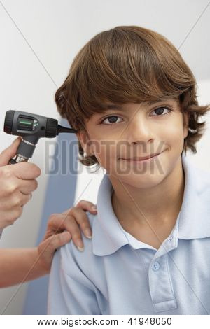 Doctor checking boy's ear with otoscope in clinic